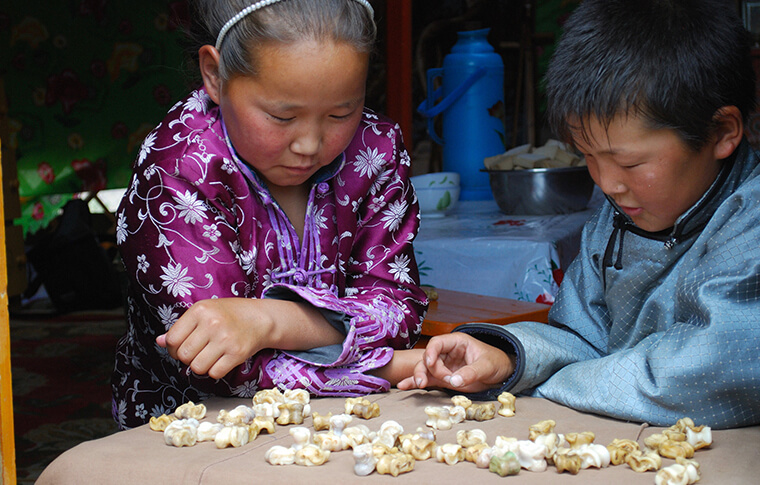 2 small children playing with some toys on a table