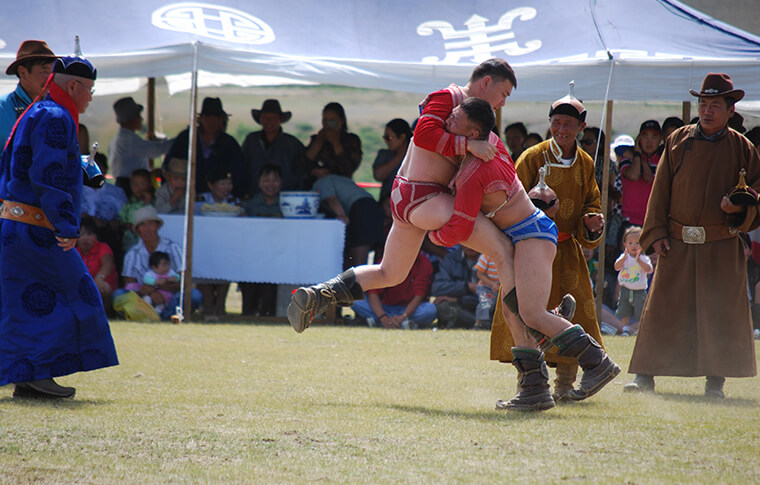 2 men in colourful outfits wrestling at a local festival