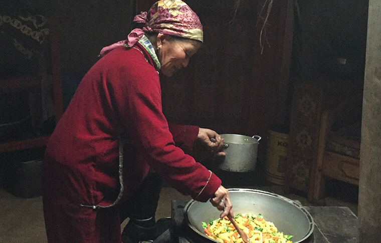 Local lady stirring a bit pot of food with a smile on her face