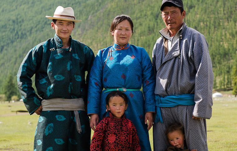 Mongolian family in traditional clothing posing for a photo