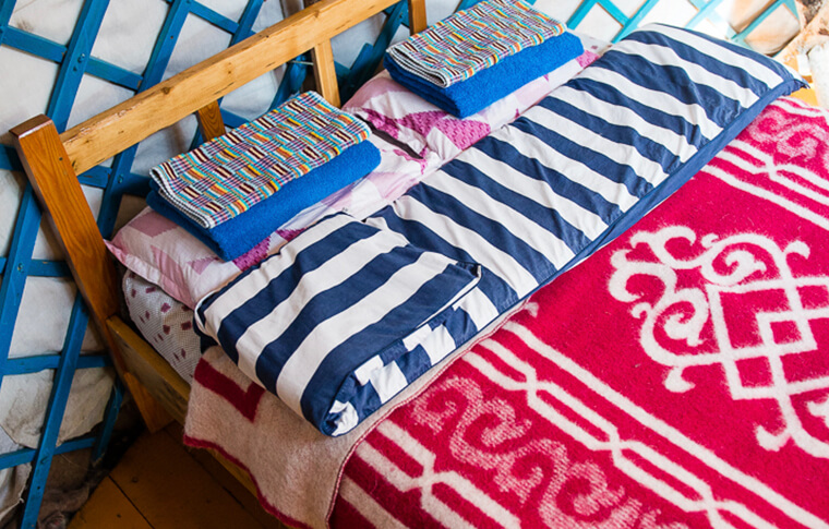 Double bed covered in colourful red, blue and white sheets